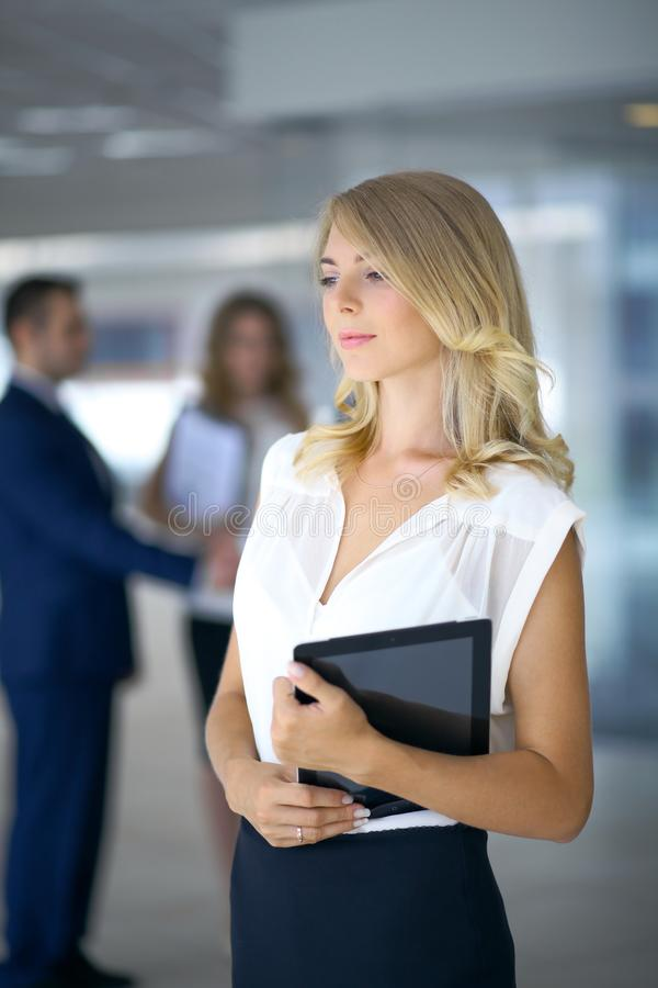Business woman standing straight and smilling in office royalty free stock photography