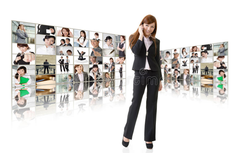 Business conferencing and global communications. Business women talk on cellphone in front of video wall. Business conferencing and global communications concept stock images