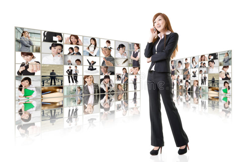 Business conferencing and global communications. Business women talk on cellphone in front of video wall. Business conferencing and global communications concept royalty free stock photo
