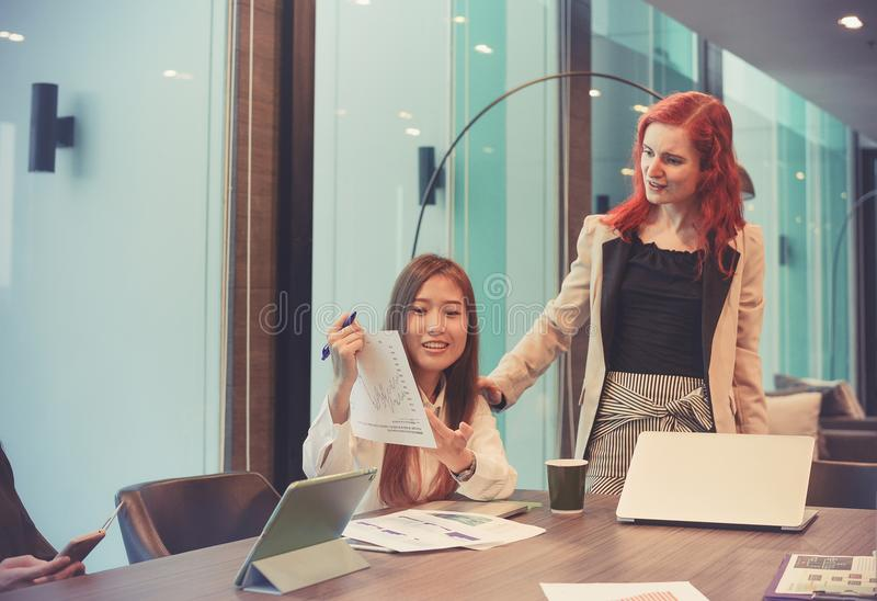Business women talking to each other in meeting room, Multi ethnic stock image