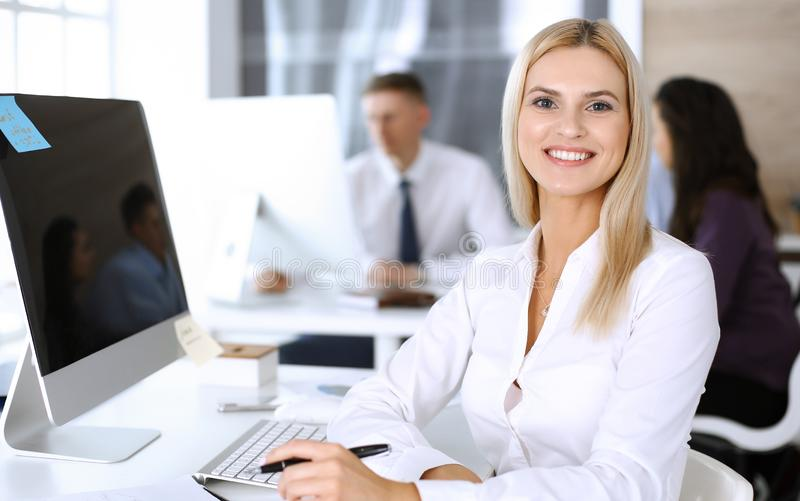 Business woman using computer at workplace in modern office. Secretary or female lawyer smiling and looks happy. Working. Business women using computer at stock image