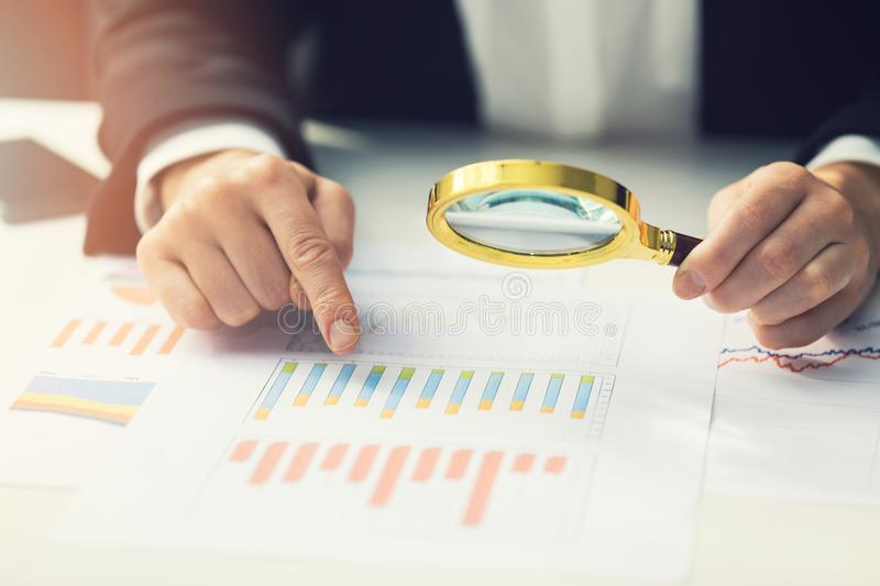 business women using magnifying to review financial report stock image