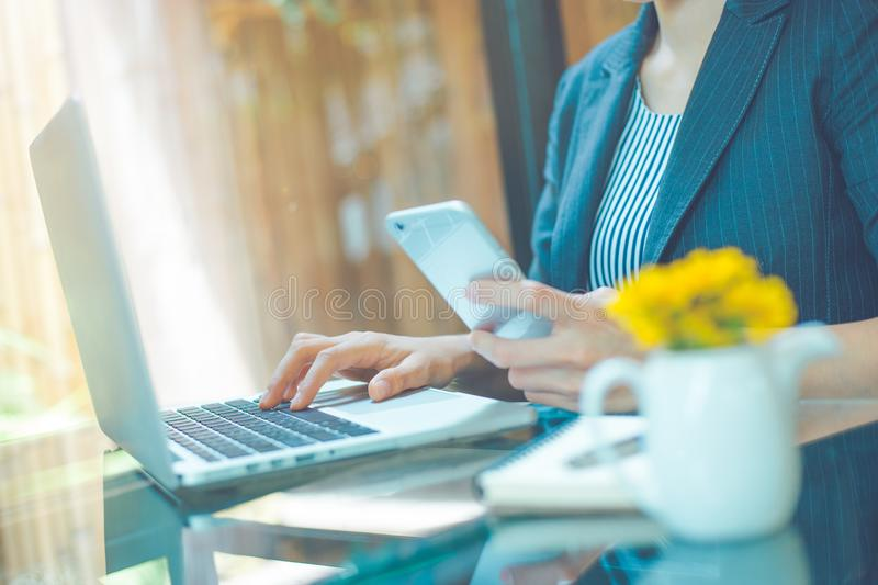 Business women work in a laptop computer and use a cell phone in royalty free stock photos