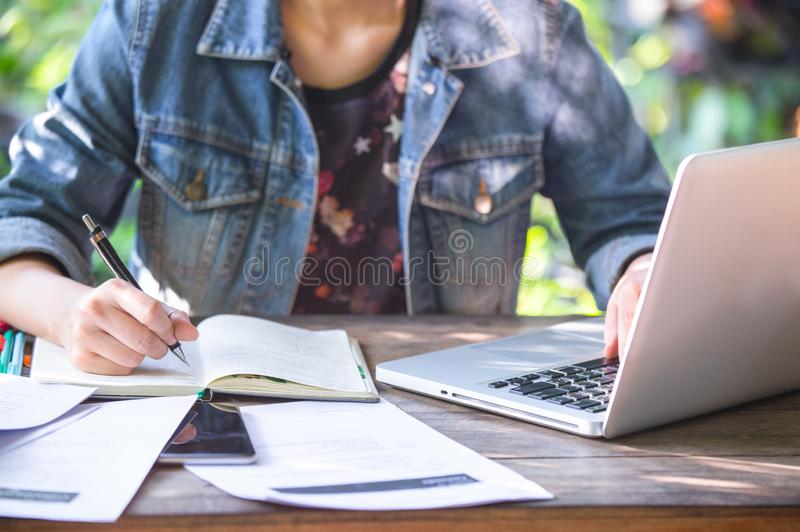 A business women is working on desk office with her computer laptop and writing accounts for investment. stock image