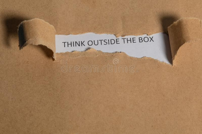 The business word Think Outside the Box written on vintage paper. Top view. Torn paper revealing the word. Innovation and ideas stock images
