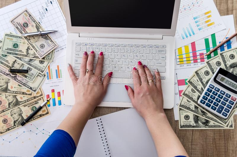 Business worker is holding US dollars in hand with laptop stock images