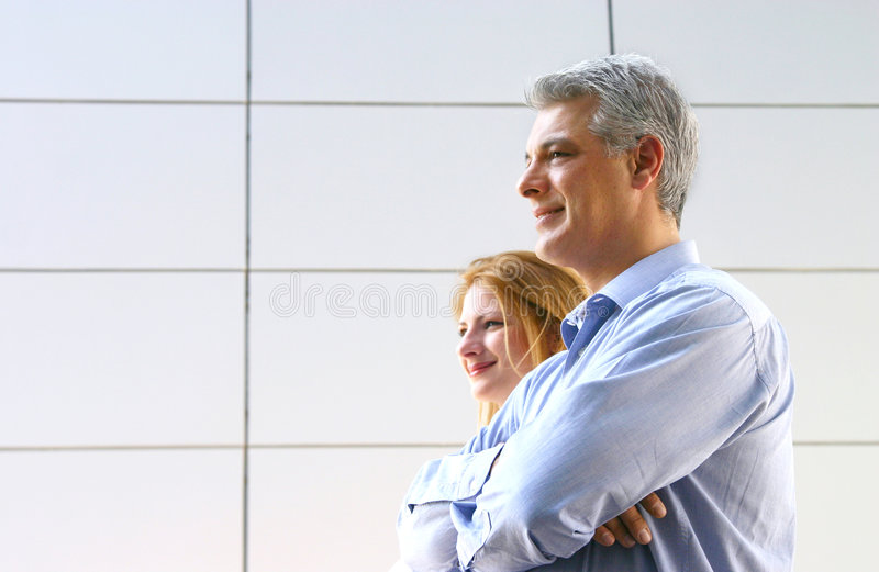 Business Workers Waiting. Two business workers, stand looking down a hallway, waiting stock photo