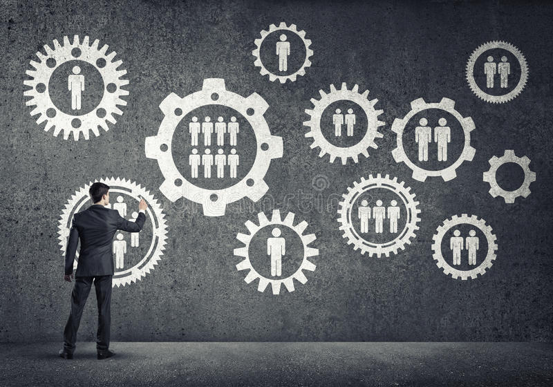 Business working mechanism. Businessman standing with back and drawing concept of teamwork and cooperation royalty free stock photo