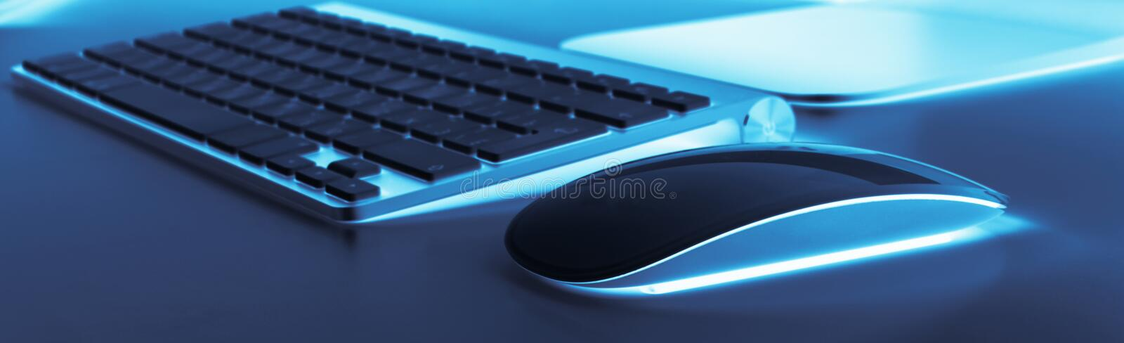 Business workplace with computer wireless keyboard and mouse on old blue table background. Office desk with copy space. stock photos