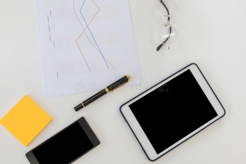 Business and Workplace concpet. Top view of work desk with blank screen tablet, smart mobile phone document paper line chart, pen royalty free stock image