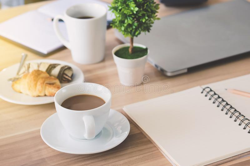 Business workplace and business objects such as laptop, note boo. K, calculator, pen, a cup of coffee, flower, bread, image bar graph etc.Focus cup of coffe royalty free stock photography