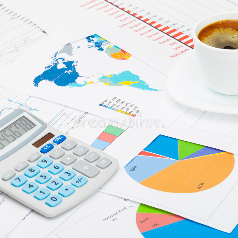 Business world and its symbols - close up studio shot of a coffee cup and a calculator over some charts stock photography