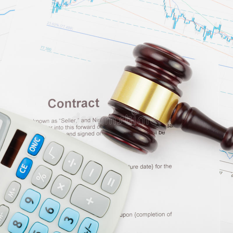 Business world and its symbols - wooden judge`s gavel and calculator over some documents stock photography