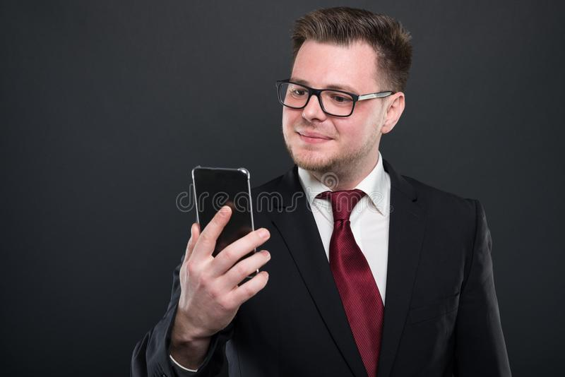 Business young man looking at black smartphone royalty free stock photos