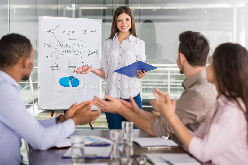 Business. Young business people sitting at meeting room and listening speaker stock image