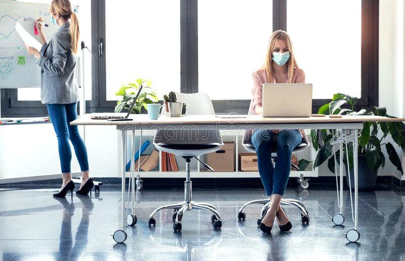 Business young women wearing a hygienic facial mask working in the office while keeping safe distances royalty free stock images