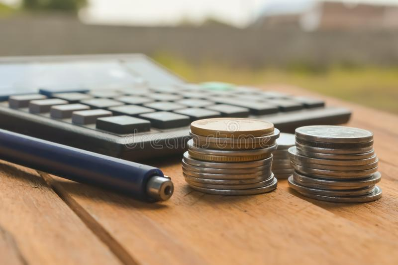 Ballpen and coins or calculate on table. Businessan man top 3 items on wooden table,coins and calculate or ballpen, chart, analysis, profit, banker, information stock image