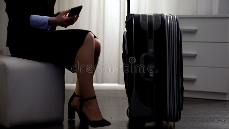 Businesslady med bagage som sitter i hotellrum och att kalla taxien som bokar service royaltyfri bild