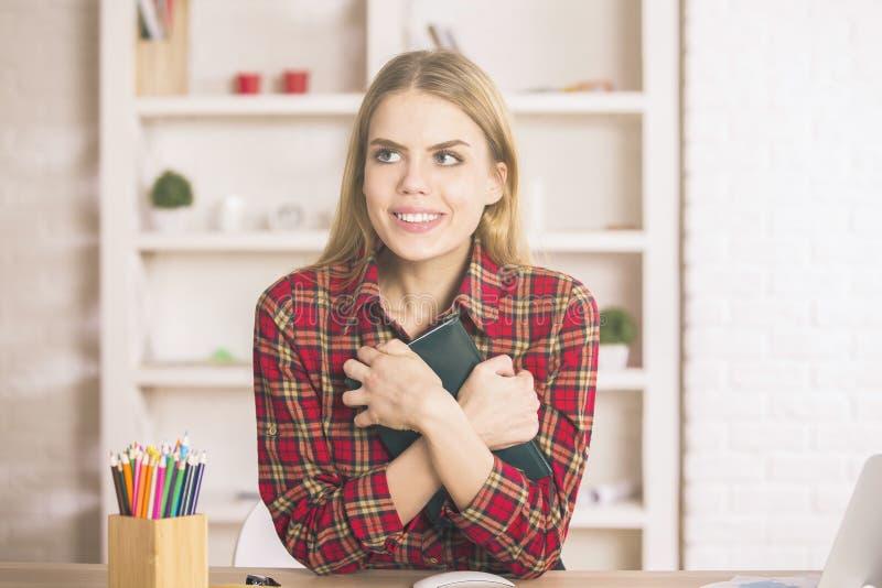 Businesslady mit dem Notizblock, der am Arbeitsplatz lächelt stockbild