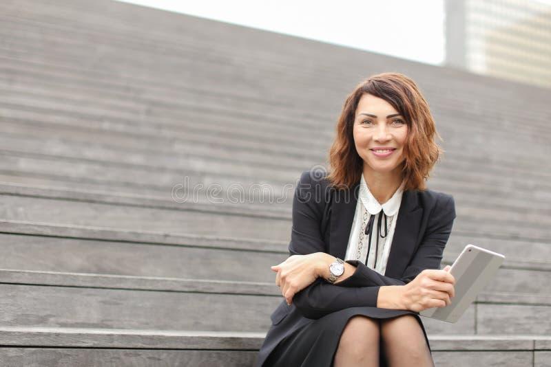Businesslady que senta-se em escadas com tabuleta e trabalho imagem de stock