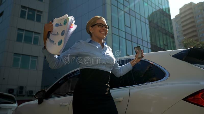 Businesslady szczęśliwy z inwestycją czyta wiadomość pomyślny transza na telefonie zdjęcia stock