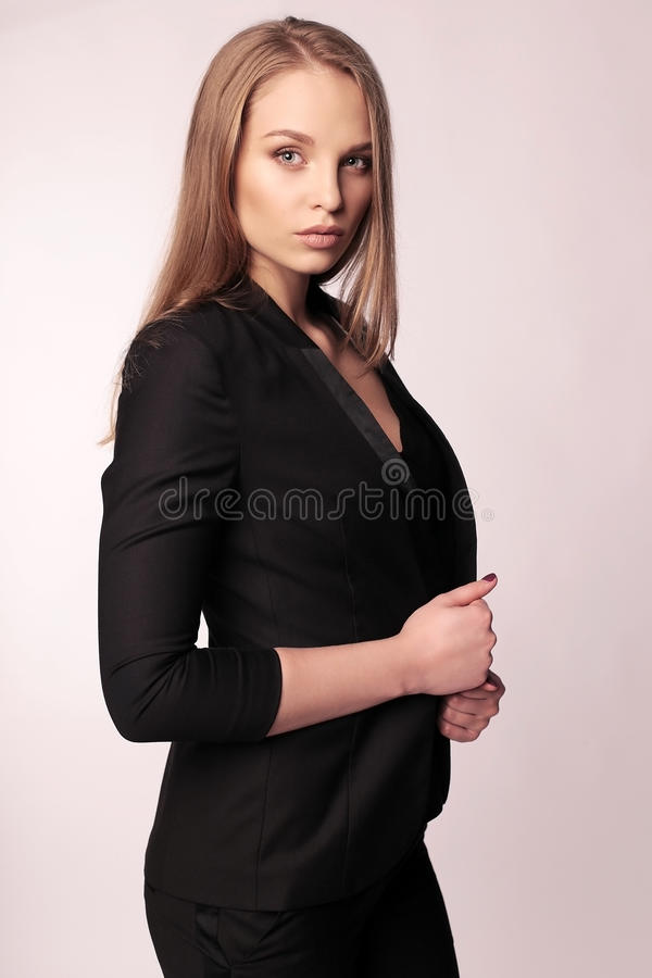 Businesslike woman with blond straight hair in elegant office outfit. Fashion studio photo of businesslike woman with blond straight hair in elegant office stock photo