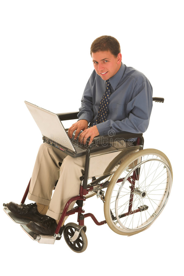Businessman #137. Businessman sitting in a wheelchair working on laptop royalty free stock photography