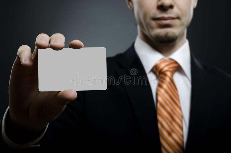 Businessman. In black costume and orange necktie reach out on camera and show credit card or visiting card, close up royalty free stock images
