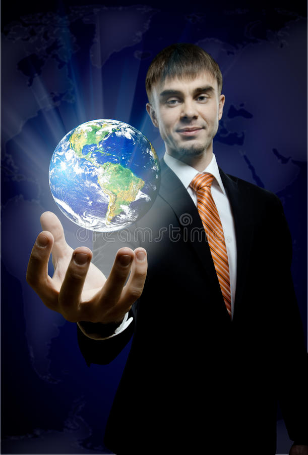 Businessman. Hold in hand terrestrial globe, on dark blue background, business concept image planet by: Stokli, Nelson, Hasler Laboratory for Atmospheres royalty free stock images