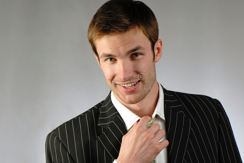 Businessman. Young businessman corrects for tie stock image