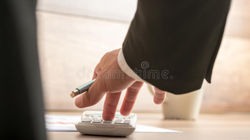 Businessman or accountant doing important financial calculation. On a manual desk top calculator, low angle view between his arm and body of the paperwork royalty free stock image
