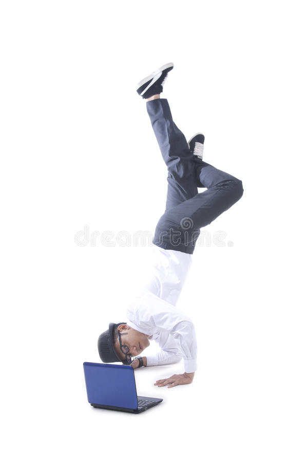 Businessman acrobat while using his laptop. Asian businessman with hat doing a handstand while using his laptop royalty free stock photography