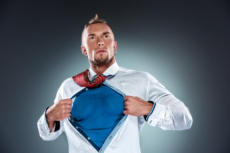Businessman acting like a super hero and tearing stock image
