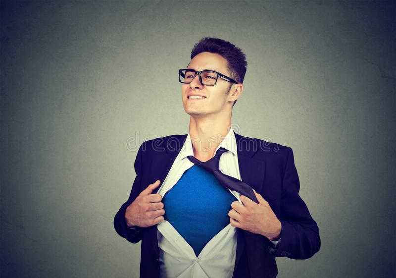 Young businessman acting like a super hero tearing his shirt off royalty free stock images