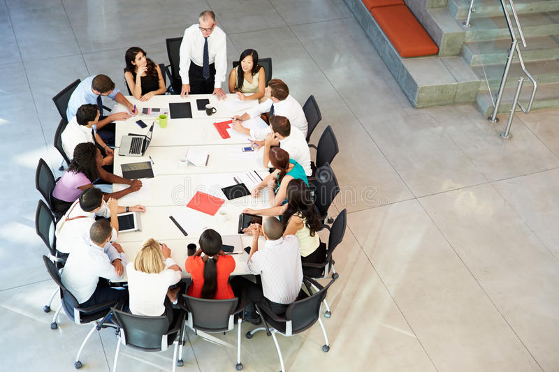 Businessman Addressing Meeting Around Boardroom Table stock photo