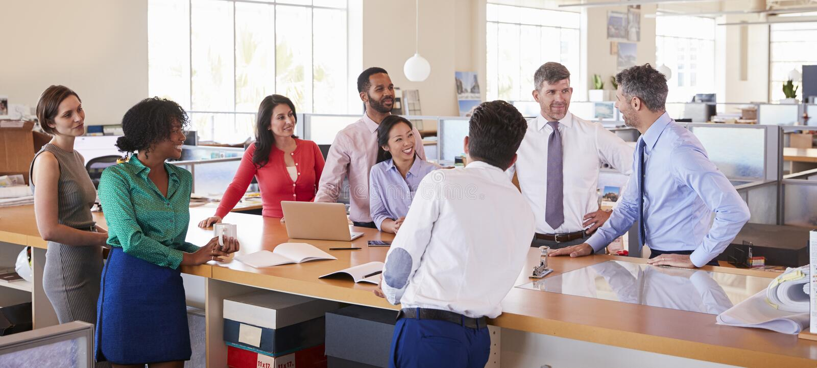 Businessman addressing team in open plan office, panoramic stock photography