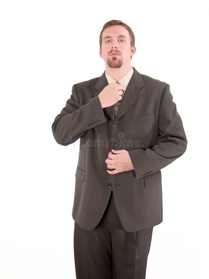 Businessman adjusting tie stock images
