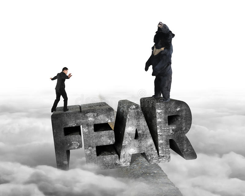 Businessman against bear balancing on fear 3D word with cloudy. Businessman against black bear standing on fear 3D mottled concrete word, balancing on ridge with royalty free stock images