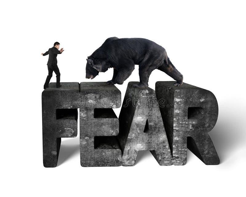 Businessman against black bear balancing on 3d fear concrete word. Businessman against black bear balancing on 3d fear mottled concrete word with white stock image