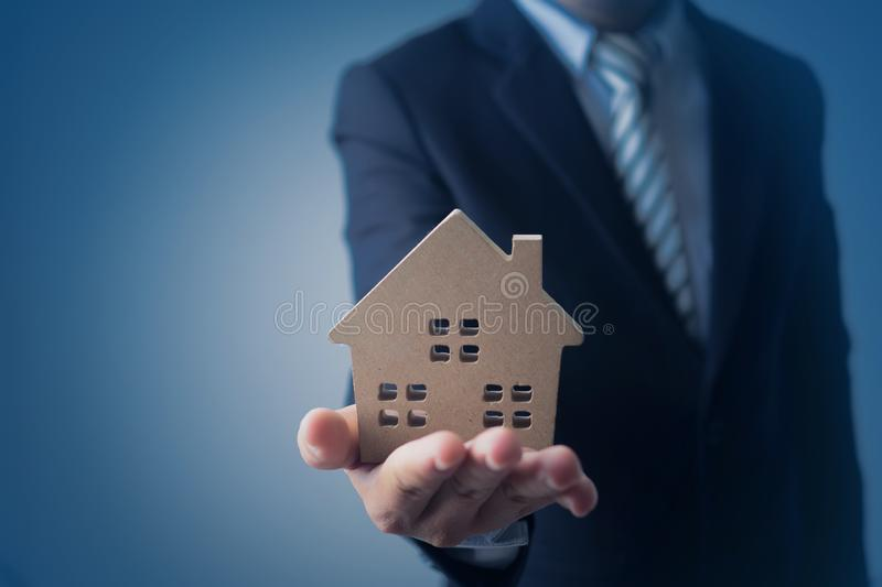 Businessman, agency banker holding house model and present real estate on dark blue background. Residence, owner, new, security, showing, agreement, customer royalty free stock photo