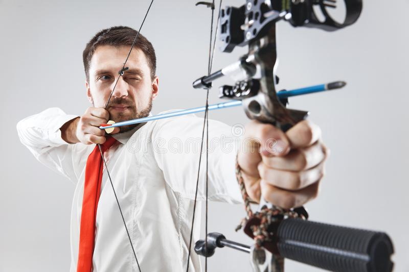 Businessman aiming at target with bow and arrow, isolated on white background stock image