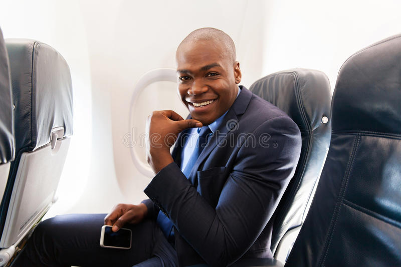 Businessman on airplane royalty free stock image