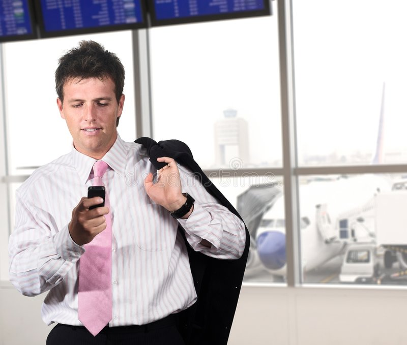 Businessman on the airport. Businessman is waiting for his flight on the airport. He is playing a game or dialing someone on his mobile