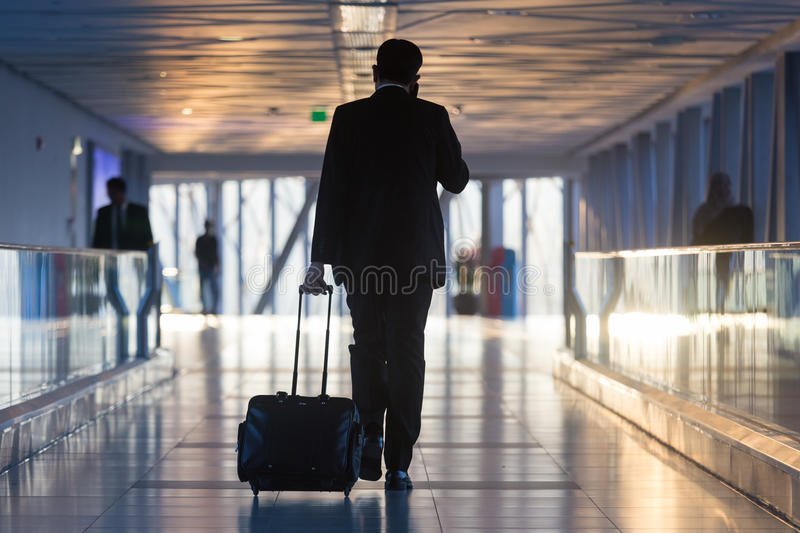 Businessman at airport corridor walking to departure gates. Businessman dragging a small carry on luggage suitcase at airport corridor walking to departure stock photo
