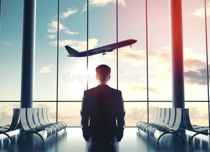 Businessman in airport and looking at airplane stock images