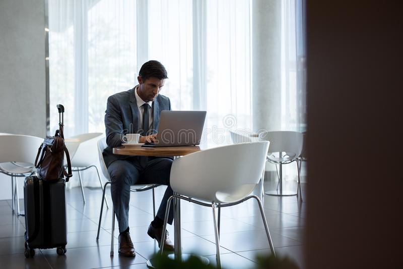 Businessman at airport waiting area. Businessman sitting in airport waiting area and working on laptop. Businessman at airport waiting lounge using laptop royalty free stock image