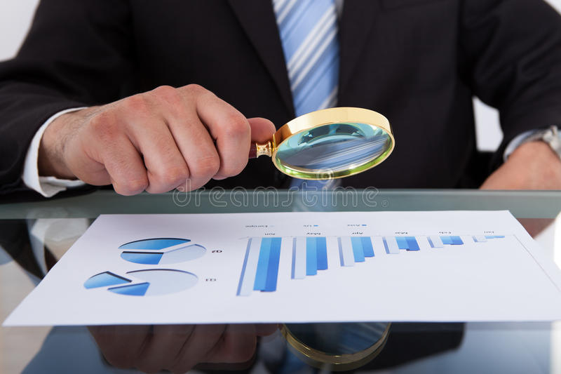 Businessman analyzing bar graph through magnifying glass royalty free stock photos