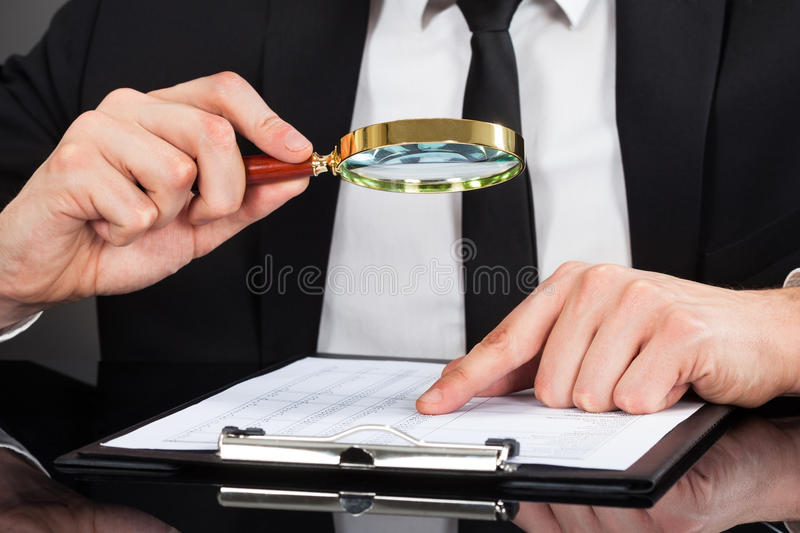 Businessman analyzing document with magnifying glass at desk royalty free stock images