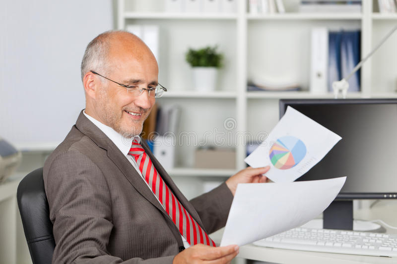 Businessman Analyzing Documents At Office Desk royalty free stock photos