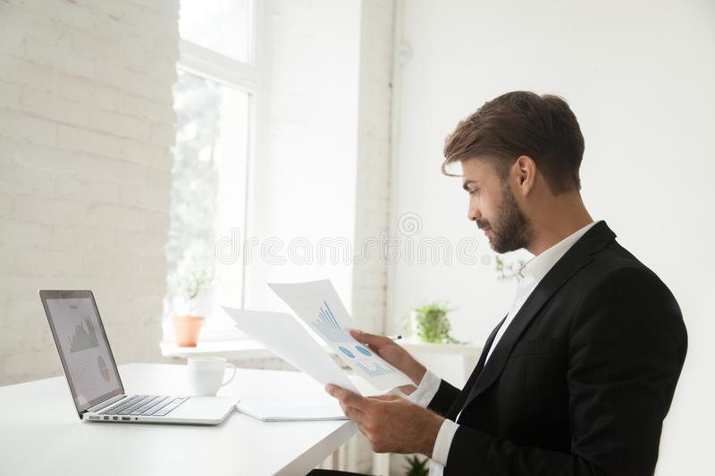 Businessman analyzing financial project statistics report satisf. Young businessman in suit analyzing financial project statistics report satisfied by business stock photography